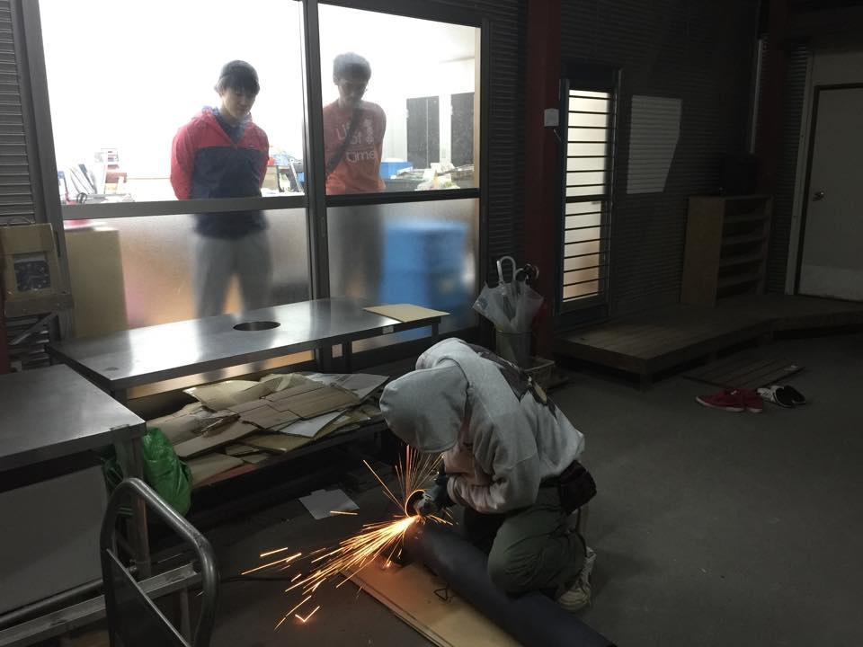 煙突加工をする小関さんと、それを覗き込む弊社スタッフ
