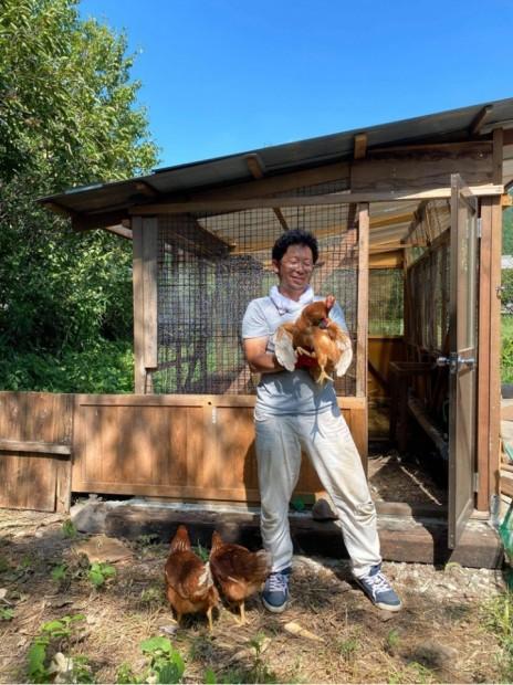 自分で建てた小屋の前で鶏を抱きながら記念撮影
